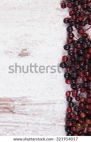 Autumn fresh elderberry and copy space for text on old rustic wooden background, healthy nutrition, alternative medicine and therapy - stock photo