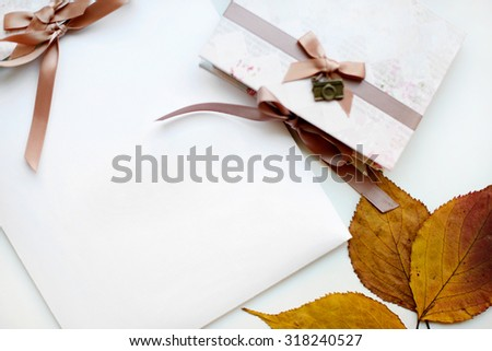 Autumn gift in craft paper and dry leaves with free space - stock photo