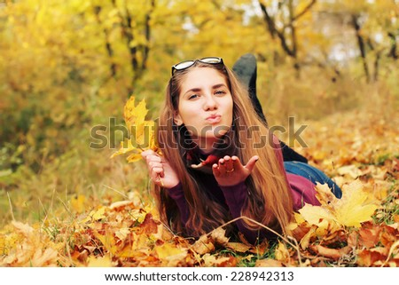 Autumn girl playing in city park. Fall woman portrait of happy lovely and beautiful Caucasian young hipster woman in forest in fall colors. Photo toned style instagram filters - stock photo
