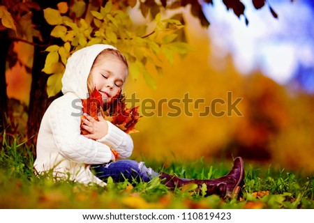 autumn happy little girl has fun playing with fallen golden leaves - stock photo