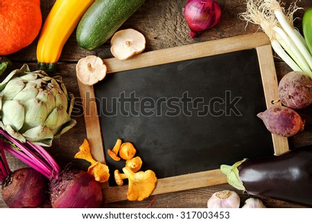 Autumn harvest around a blank vintage slate with artichoke, aubergine, mushrooms, squash, marrows, onion, beetroot, and spring onion, overhead view with copyspace for your recipe or menu - stock photo