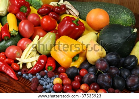 Autumn harvest - ripe fruit and vegetables. Organic produce. Tomatos, plums, raspberries, zucchini, pears and other food. - stock photo