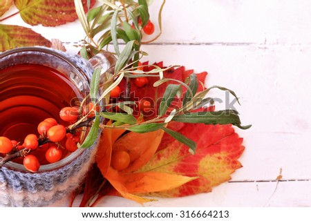 autumn herbal  tea sea buckthorn knitted in a mug on a white wooden background - stock photo