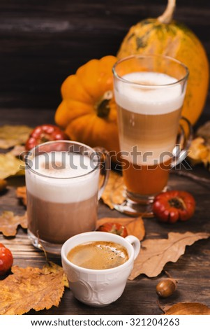 Autumn hot coffee drinks. Pumpkin latte, hot chocolate and espresso on rustic wooden background. Fall concept. Selective focus. Toned image - stock photo