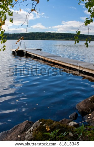Autumn image of pier on lake in Finland. With colored leaves in foreground - stock photo