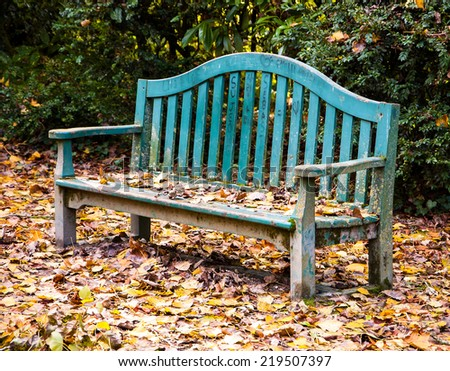 Autumn in the park. Golden leaves on the old wooden bench and on the ground. Love declaration on bench's planks (French and Asian language characters, heart shape). - stock photo
