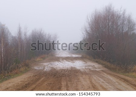 autumn landscape dirt road near a forest in the fog - stock photo