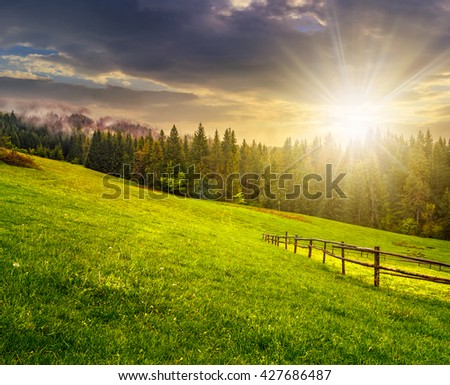 autumn landscape. fence on the hillside meadow near forest in mountain in evening light - stock photo