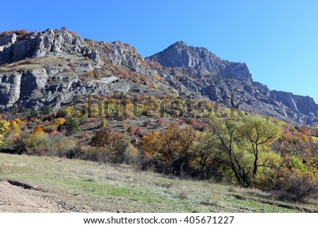 autumn landscape road in the mountains on a sunny autumn day - stock photo