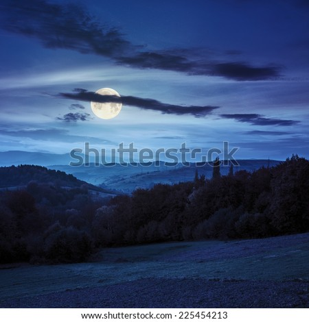 autumn landscape. village on the hillside behind forest on the mountain at night in fool moon lighy - stock photo
