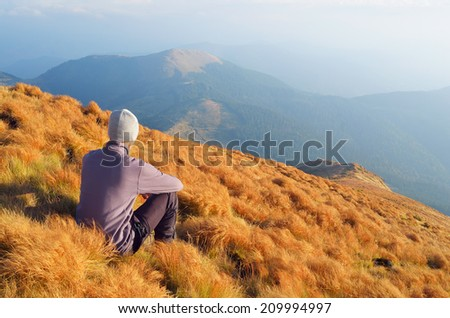 Autumn Landscape with a man sitting on the hillside. Outdoor recreation - stock photo