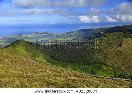 Autumn landscape with hills, yellow grass, forest and cloudscape on San Miguel island, Azores, Portugal