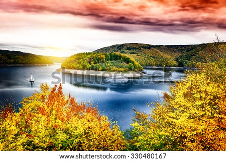 Autumn landscape with spectacular sunset over river - stock photo