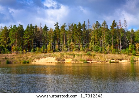 Autumn lanscape with pine forest and lake - stock photo