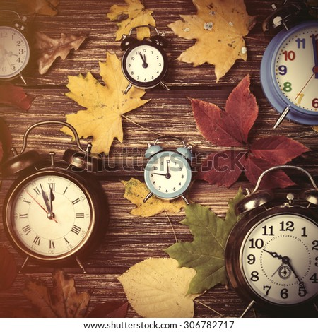 Autumn leafs and alarm clock on wooden table. - stock photo