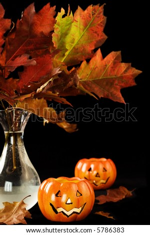 Autumn leaves and halloween pumpkins in the dark - stock photo
