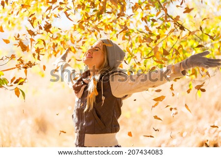 autumn leaves falling on happy young woman in forest - stock photo