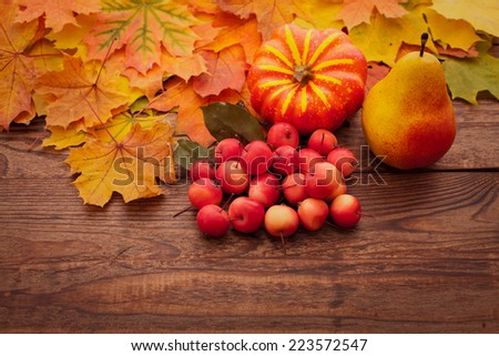 Autumn leaves on wooden table. Fruits and vegetables, apple, pear, pumpkin  - stock photo