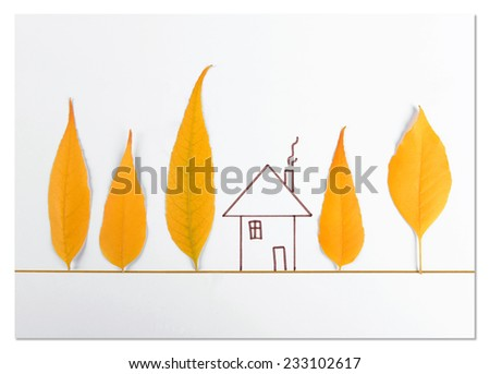 Autumn leaves with painted house on white paper - stock photo