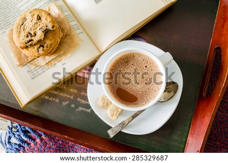 Autumn lifestyle - hot chocolate, chocolate chip cookies, old book, tray, warm blanket, rustic wood background, top view - stock photo