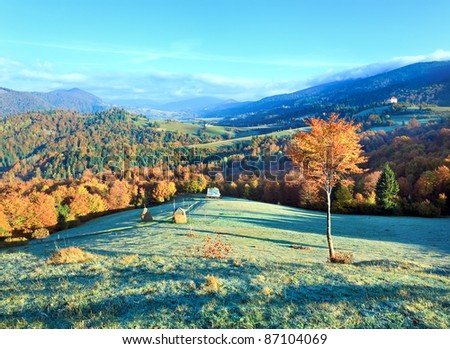 Autumn misty morning mountain valley with stack of hay (Mighgirya village outskirts, Carpathian Mt's, Ukraine). - stock photo