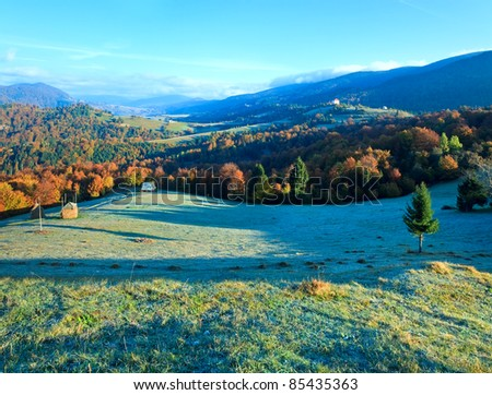 Autumn misty morning plateau with stack of hay and country house (Mighgirya village outskirts, Carpathian Mt's, Ukraine). - stock photo