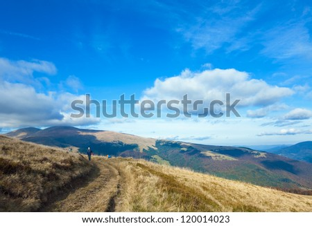 Autumn misty mountain view with country road and woman (Carpathian Mt's, Ukraine). - stock photo