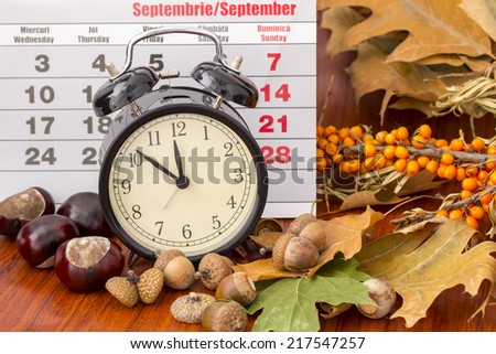 Autumn months September calendar with table clock, brown acorns,  chestnuts, rosehip, seabuckthorn, autumn leaves, on wooden background - stock photo