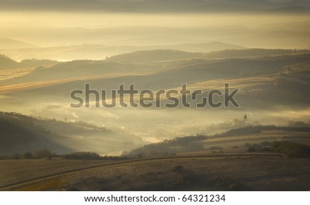 autumn morning with fog and sun rising over a mountain village - stock photo