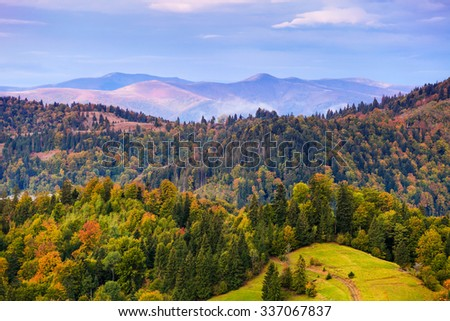Autumn mountain landscape with colorful trees in forest. Sky with clouds over hazy hills - stock photo