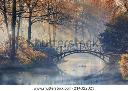 Autumn - Old bridge in autumn misty park - stock photo