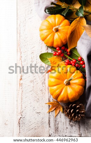 Autumn old wood background with pumpkin, pine cone, berries, yellow leaves and rowan. Selective focus. With copy space. Top view. - stock photo