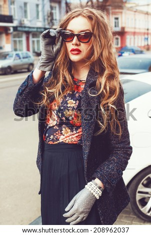 Autumn outdoor fashion portrait of elegant woman posing at the street, wearing vintage coat retro cat eye sunglasses and pearl jewelry. Old european city, warm toned colors. - stock photo
