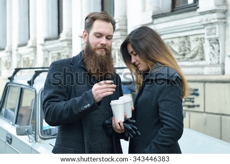 Autumn outdoor fashion portrait of young couple drinking coffee and smoking outdoor, image toned and noise added - stock photo