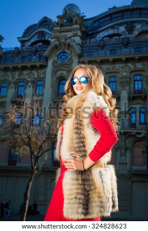 Autumn outdoor Fashion portrait of young woman wearing red dress,fur vest and sunglasses.Fashion style portrait. Young elegant woman in red long dress posing against old city building.Winter fashion. - stock photo