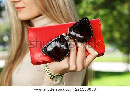 autumn outdoor fashion young woman hold red purse clutch in hand with black trendy sunglasses - stock photo