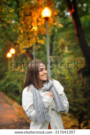 Autumn outdoor portrait of a smiling woman wearing knitted jacket. - stock photo