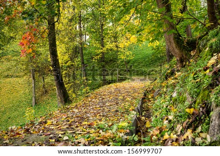 autumn park with a pathway on a slope - stock photo