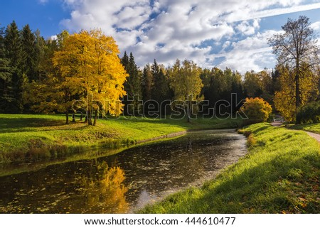 Autumn park with pond, colorful trees, yellow leaves, sunlight and blue sky with clouds. Nature Russia - stock photo