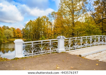 Autumn park with white wooden bridge and openwork fence in Pushkin, Tsarskoe Selo, St. Petersburg, Russia. - stock photo