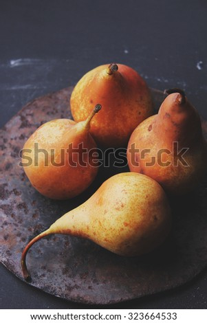 autumn pears on a black background - stock photo