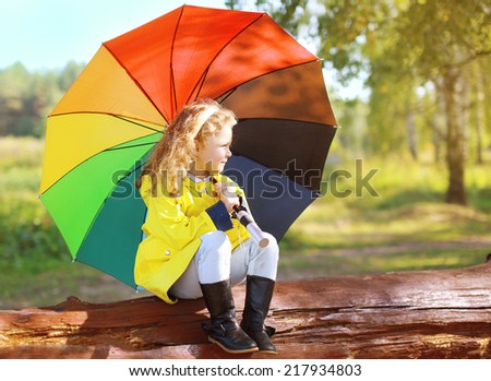 Autumn photo, little child with colorful umbrella outdoors - stock photo