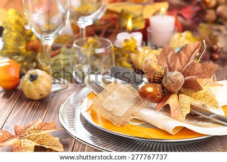 Autumn place setting with leaves, candles and pumpkins. - stock photo