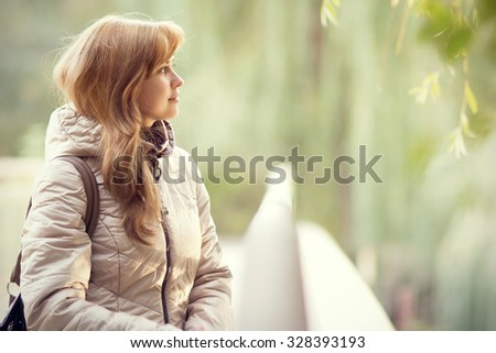 Autumn portrait of a beautiful young woman on the bridge - stock photo