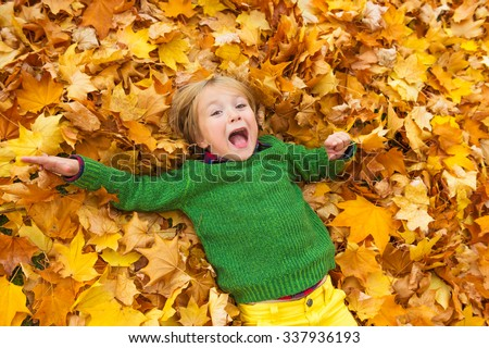 Autumn portrait of a cute little boy of 4 years old, playing with yellow leaves in the park, wearing green pullover - stock photo
