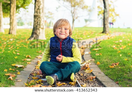 Autumn portrait of a cute little boy of 4 years old, playing with yellow leaves in the park, wearing blue jacket and green trousers - stock photo