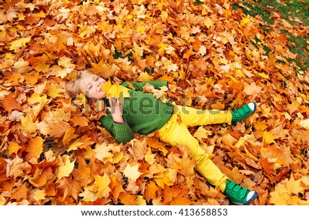 Autumn portrait of a cute little boy of 4 years old, playing with yellow leaves in the park, wearing yellow trousers, green pullover and shoes - stock photo