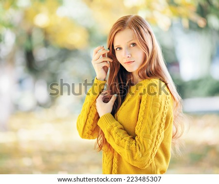 Autumn portrait of a young cute redhead woman in yellow sweater  - stock photo
