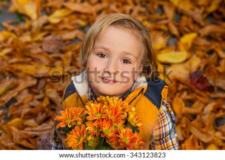Autumn portrait of adorable little blond boy of 4 years old, wearing warm yellow vest coat, holding small bouquet of orange chrysanthemum flowers - stock photo