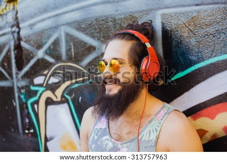 Autumn portrait of hipster man outdoors portrait.Stylish man posing on the wall,ready to car trip.Happy and active.mans fashion sunglasses,Young sportsman,young dj,t-shirt and shorts.earphones - stock photo